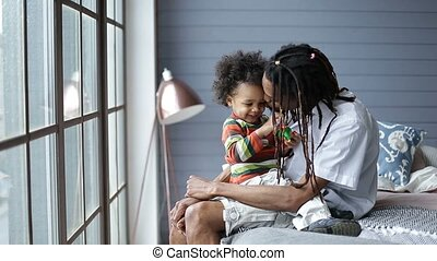 Mixed race boy sitting on father's lap at home
