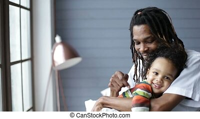 African american father embracing his little son