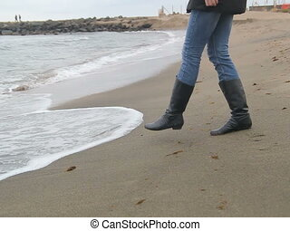 Woman on the cold icy beach playing with waves of sea, pov