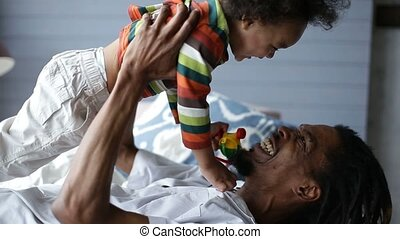 Playful father lifting son up while lying on bed - Positive...