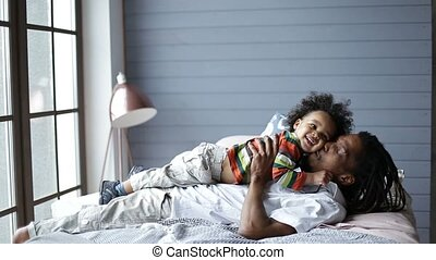 Happy father lying on bed and playing with son - Happy...