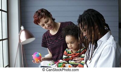 Lovely mixed race toddler having fun with parents - Cute...