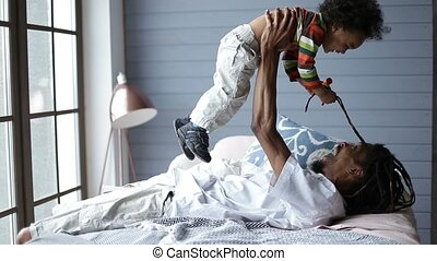 Happy father lifting his cute son up in the air - Happy...