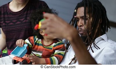 Positive african father playing with toddler son