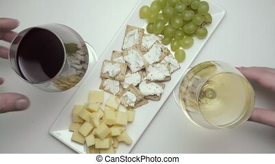 Two glasses of wine, red and white, with snacks. Top view