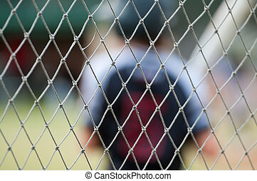 Close up of baseball fence - Baseball player out of focus...
