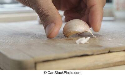 Crashing garlic cloves with chef knife - Shot of Crashing...