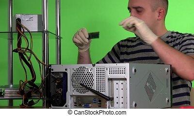 Bald computer specialist installing ram memory into desktop...