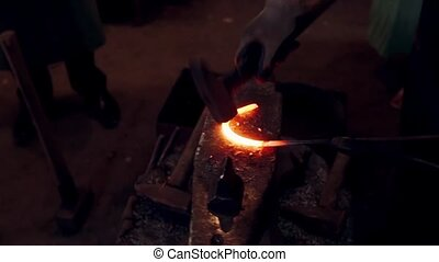 Close-up view of blacksmith working with hammer and hot red...