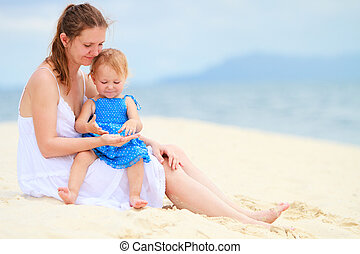 Young family at beach - Young mother and her little toddler...