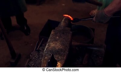 A blacksmith forging a horseshoe with a hammer on anvil at...