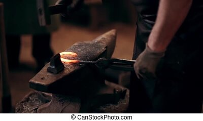 Blacksmith working with hammer and metal. Man making horseshoe on the anvil in smithy. Close-up view of workplace.