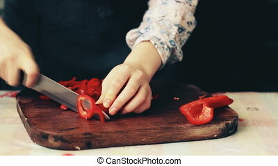 Woman's hands slicing sweet Red Bell Pepper on a wooden...