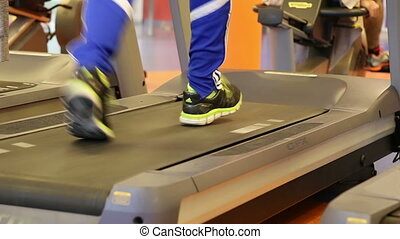 Close up of legs running on a treadmill in a gym - Shot of...