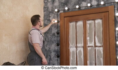 Worker screws bulbs into design lightning around door inside...