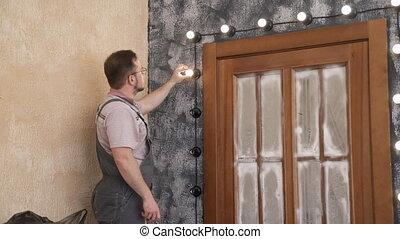 Worker screws bulbs into design lightning around door inside...