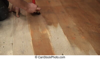 Master using broad brush causes the brown paint on the wooden floor.