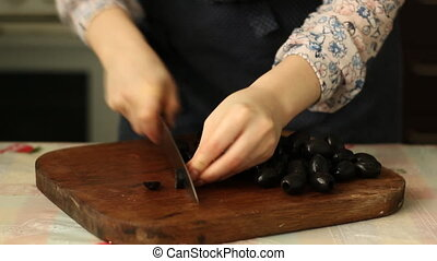 female cutting olives for a salad