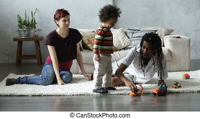 Happy interracial family playing with car toys - Positive...