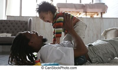Cheerful father and toddler son having fun at home -...