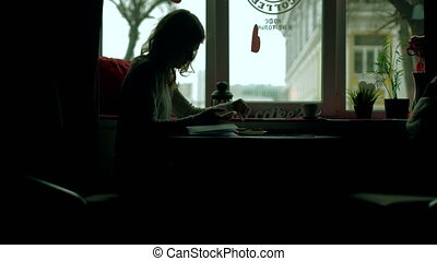A girl in a cafe drinks cappuccino phone
