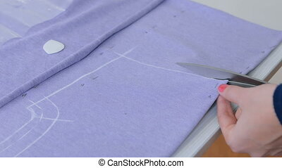 Hands of seamstress cutting fabric with scissors -...