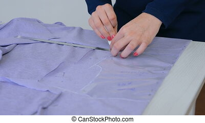 Tailor, designer drawing line on fabric at sewing studio -...