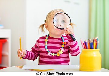 Toddler girl looking through magnifier - Funny photo of...