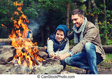 father and son roasting marshmallow over campfire - camping,...