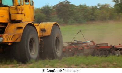 Plow for plowing fields - Big tractor plow a field with a...