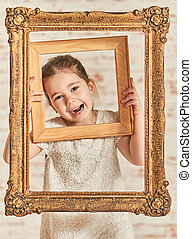 Indoor portrait of an expressve adorable young little girl -...