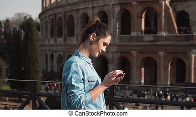 Young woman uses her smartphone in Rome, Italy against the...