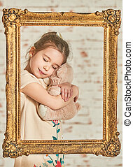 Little girl playing with teddy bear - Indoor portrait of an...