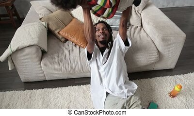 Loving african american father lifting his son up - Loving...
