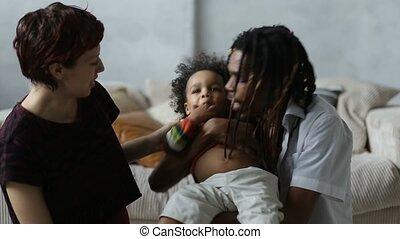 Affectionate mixed race parents kissing little son -...