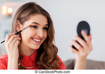 woman with eye shadow brush and mirror does makeup - beauty,...