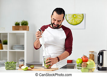 man with blender cooking food at home kitchen