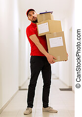 delivery man with parcel boxes in corridor
