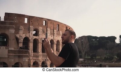 A handsome man visiting Rome, Italy, takes photos near the...