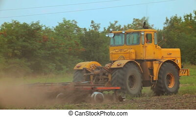 Plowing the field - A large farm tractor plowed land Behind...