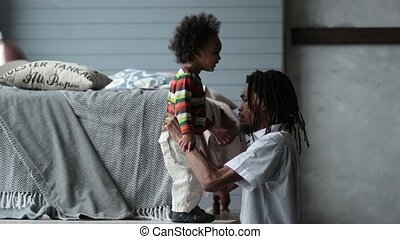 Serious african father parenting his toddler son - Handsome...