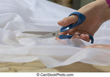 The woman cuts the fabric with scissors for sewing curtains...