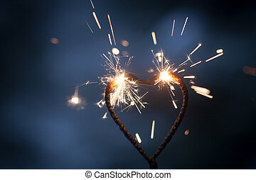 Heart shape sparkler burning and glowing in the dark
