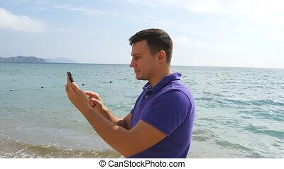 Young smiling man having a video call on smart phone at the...