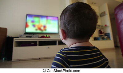 baby watching blurred content on TV - Shot of baby watching...