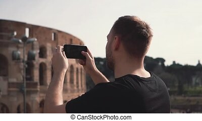 Handsome man tourist visiting Rome, Italy take photos of Colosseum. Landscape with tourists on background. Slow motion.