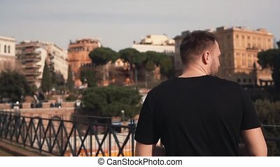 Man walk on street in Rome, Italy, turns and looks in camera. Male enjoying weather, architecture of city. Slow motion.