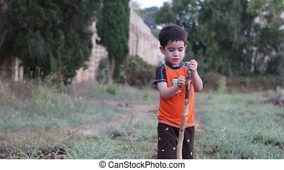 adorable kid holding tree branch outdoor - Shot of adorable...