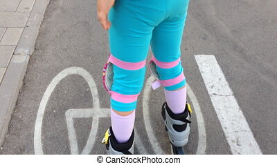 adorable girl skating on rollerblades on bicycles path -...