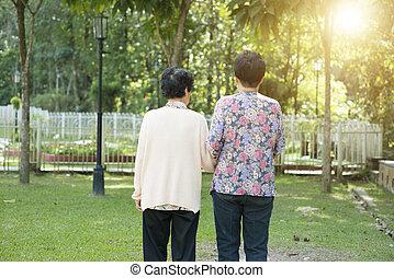 Rear view Asian elderly women walking in garden park